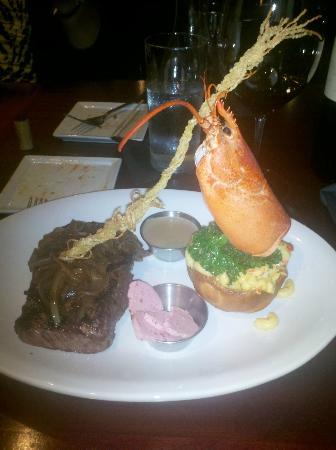 1618 West Seafood Grill: Grilled Ribeye, topped with lingonberry butter on lobster mac & cheese in a bread bowl