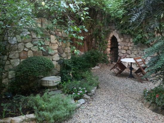 Hotel Empress Zoe: Looking out in the garden, breakfast area early in the am.