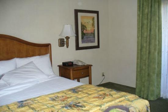 Inn of Naples: Ample room available in accommodations. Small night stand with alarm clock and phone.