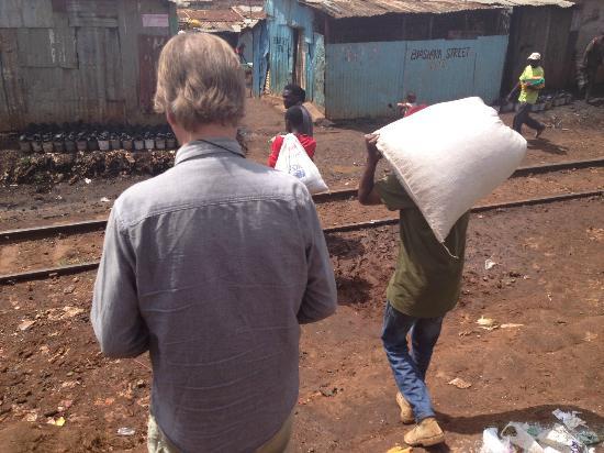Kibera Tours: husband passing the railroad in Kibera