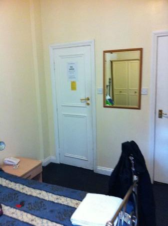 Blair Victoria Hotel: Room-door to hall on left, bathroom on right (my coat hanging there on the bed, sorry)