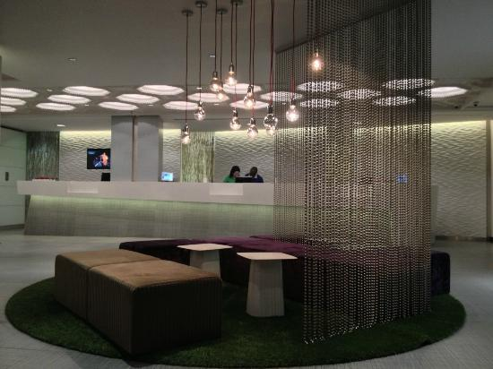 NH Brussels Bloom: View of the check in desk in the lobby from the window seating area.