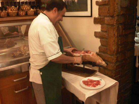 Osteria Nuovo Convento: the chef renato cutting with knife the tuscany ham