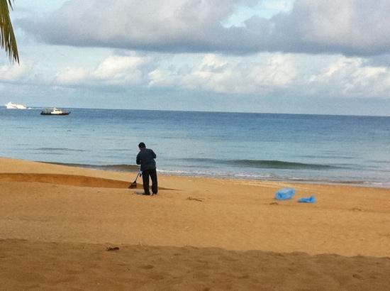 Berjaya Tioman Resort - Malaysia: A hotel worker cleaning the beach