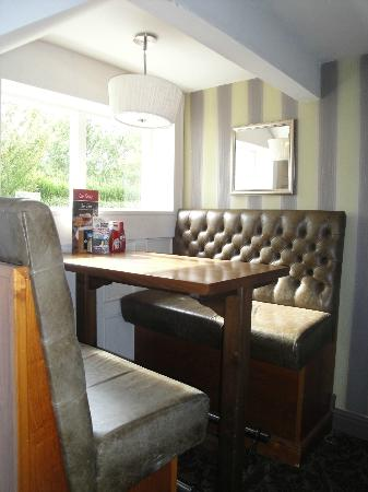 The Boathouse: Interior pub decor with pedestal table & stone-brown vinyl booths