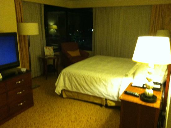 JW Marriott Washington DC: TV and bed with night view out the windows