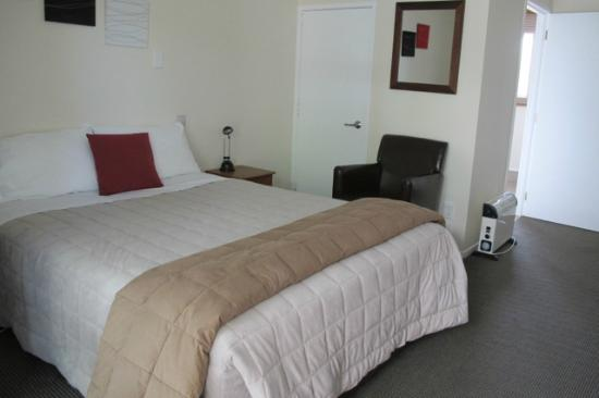 Waihi Motel: Small closet, bedside stand, chair.
