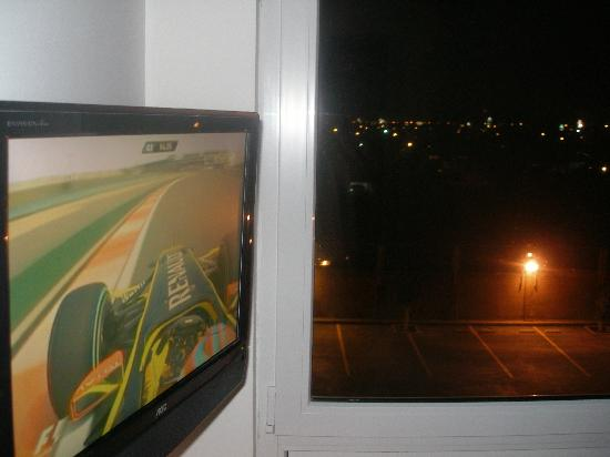 City Express Junior Mexicali: Flat screen TV & window at night.