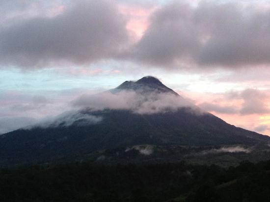 The Springs Resort and Spa: Sunset view from our balcony of the Arenal Volcano