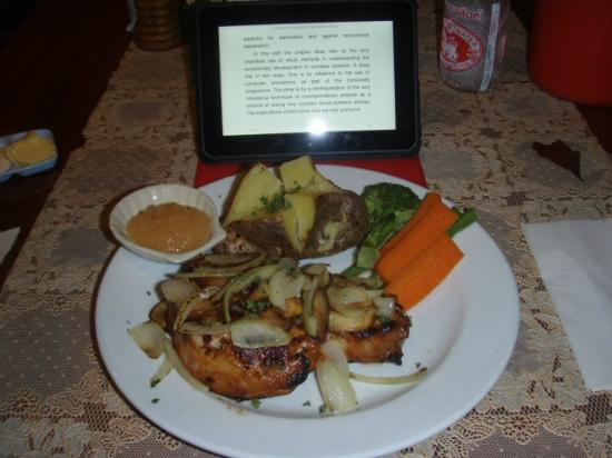 Richman Poorman Guesthouse: Massive fresh Pork Chop with a little lite reading at dinner......