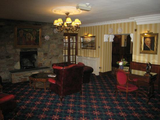 Abbeyglen Castle Hotel: Sitting room with fireplace next to reception/front desk