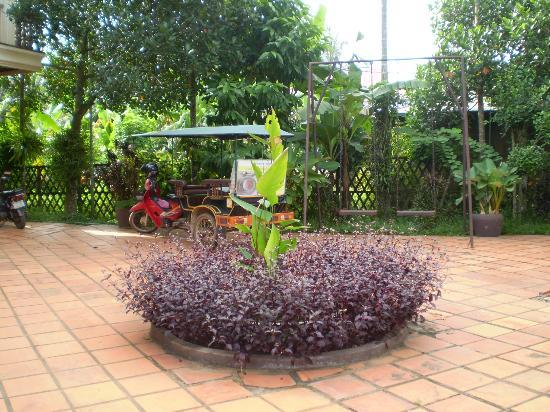 Bloom Garden Guesthouse Villa: Arty photo of red tuk tuk and whimsical garden