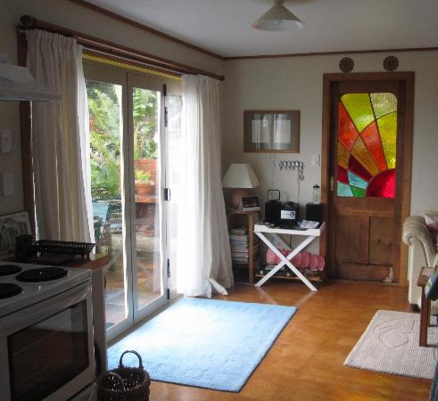 Bethells Beach Cottages: Wairua Apartment Front Door/Main Living Room/French Doors opens to Patio