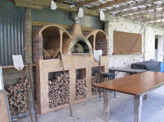 ‪بيثلز بيتش كوتدجز: Bethells outdoor wood fire pizza oven in the common area