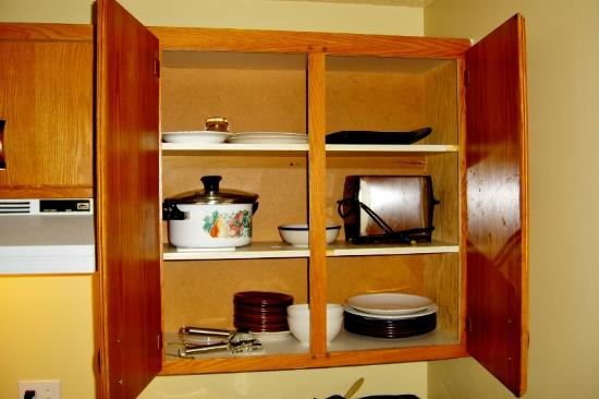 The Discovery Inn: Open cupboard with dishes. Toaster.