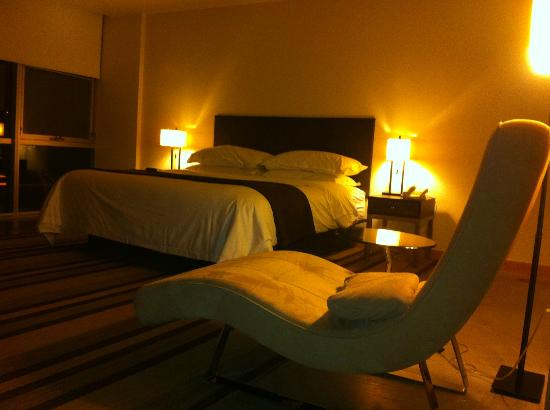 hotelVetro: studio suites & convention center: Lounge chair and bed - note big windows behind bed.