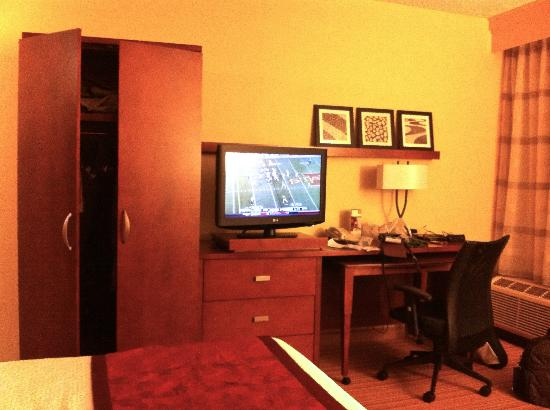 Courtyard by Marriott Indianapolis Carmel : Storage, TV, & desk across from sofa in king room