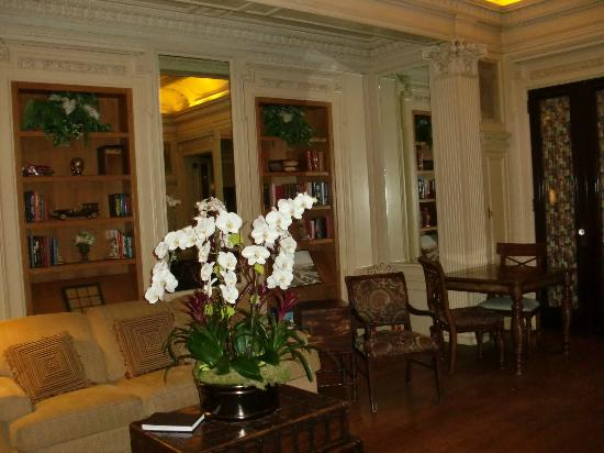 Glorietta Bay Inn: Parlor and library area with tables for breakfast - the orchids are real!