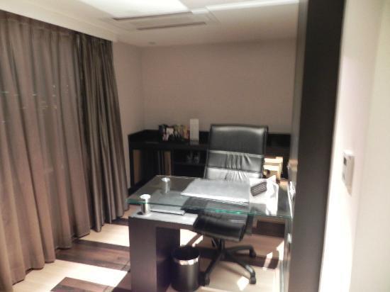Golden Tulip Mandison Suites: desk & mini bar