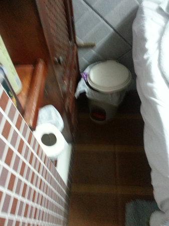 Pousada da Bruna:                   lavatorio, cesto de basura y cama al lado