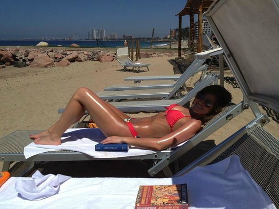 Villa Premiere Boutique & Romantic Getaway: Corinne getting some rays on the beach in front of the beachside cabanas.