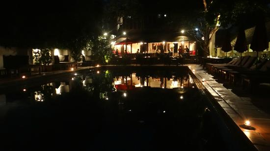 Tamarind Village: Pool Area at night with restaurant behind