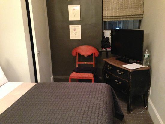 Seton Hotel: Flat screen tv, antique looking drawers and chair, and small window view air conditioner