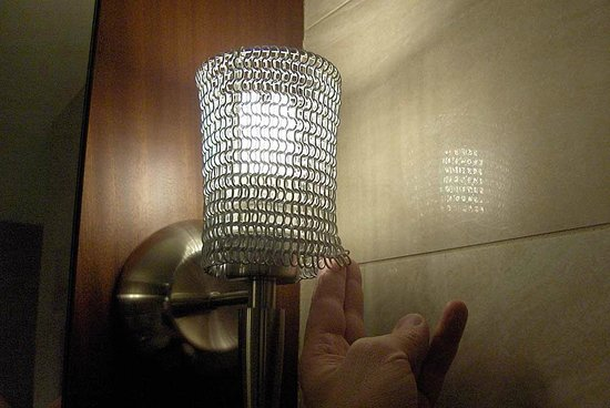Forty 1⁰ North: The bathroom light fixture(s) with chain mail shade.