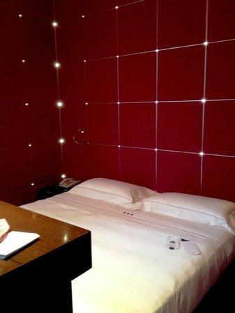 UNA Hotel Vittoria: Cama con detalles LED en la pared