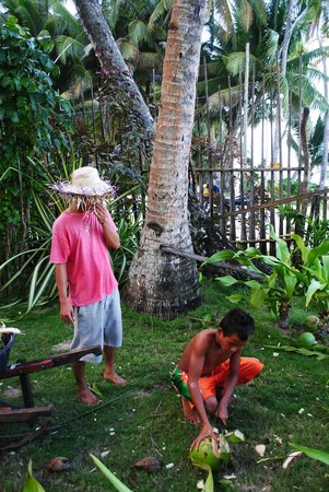 The Boardwalk at Cloud 9: Jahvanni using a machete to open a fresh coconut for post-surf treat for us
