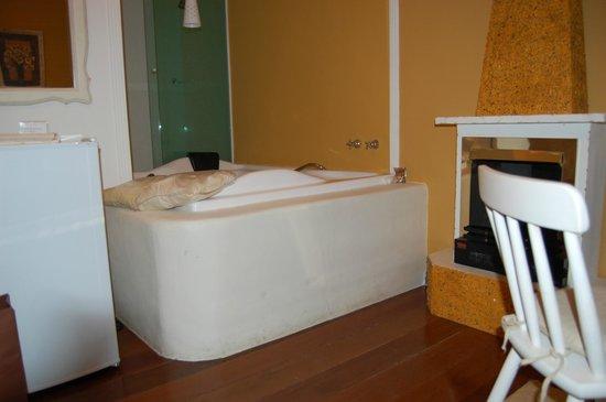 Pousada Quinta dos Passaros: Banheira emassada ligando o quarto ao banheiro.
