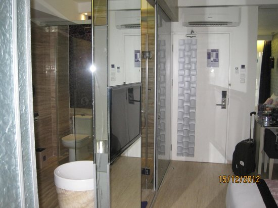 Grand Mega Resort & Spa Bali: the entrance and the divided room with the glass panelled bath compartment and WC