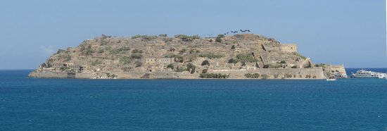 "Beach Club Aphrodite: If you've read ""Who pays the ferryman"", this is the island of Spinalonga, the lepor colony."