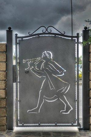B&B Qui dormi l'Etrusco: Cancello in ferro con suonatore i flauto etrusco