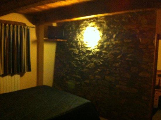 Chalet Faure & SPA: Stanza con parete in pietra a vista e soffitto in legno