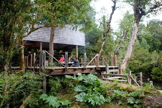 Patagonia Sur Reserves - Melimoyu: Riverside activity center equipped with open fireplace, fishing gear, a variety of kayaks, and r