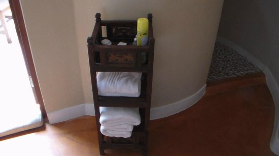 Azanzi Beach Hotel: Towel and toiletry stand in bathroom
