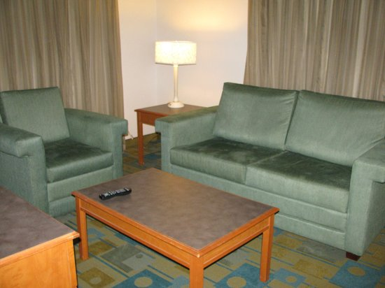 La Quinta Inn Savannah Midtown: Living room with chair, sofa, and coffee table.