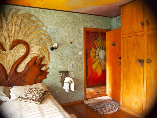 Little Paradise Lodge: One of the bedrooms, beautifully decorated with original art and carvings