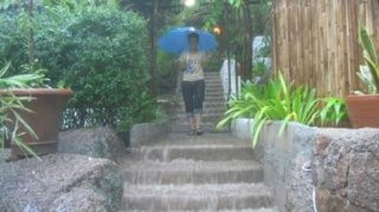 Anankhira Boutique Resort: Our host braves the waterfall stairs after 3 days of rain!