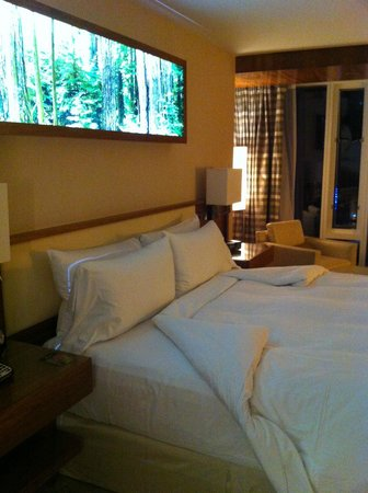 Fairmont Pacific Rim : Bed with forest scene above.