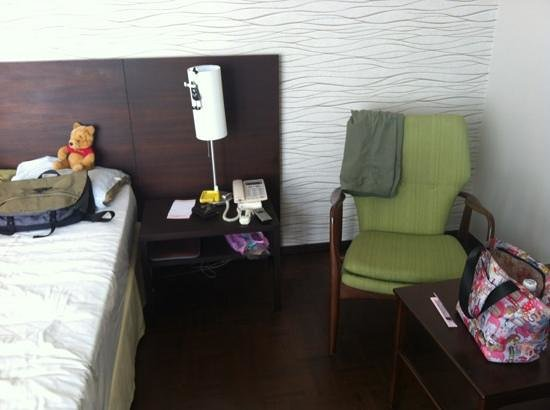 Baan Silom Soi 3: Bedside table with lamp and small seating area on the side.