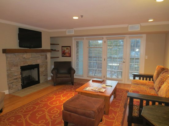 The Residences at Biltmore: Sitting area, fireplace, wall-mounted flat-screen TV, and doors to balcony, suite 404