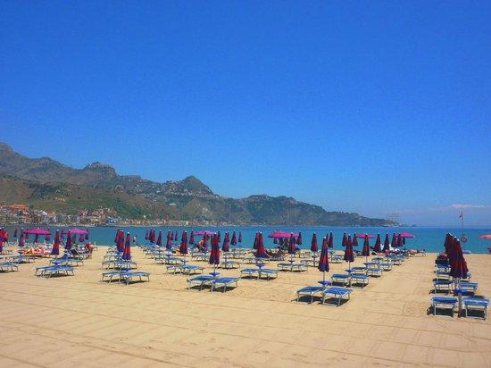Spiaggia di giardini naxos e vista sulla collina di taormina