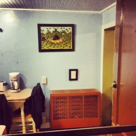 The Pines Cottages: View through the screen door to the kitchen with a cozy furnace :)