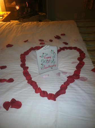 Cliffside Inn: Rose Pedals on bed with Porcelain sign saying Happy Anniversary