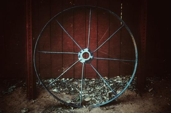 The Old Round Barn: An Old Wheel to an Old Wagon on the Outside of The Round Barn