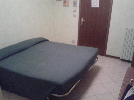 Albergo Ristorante Nazionale: Il letto è a ridosso della porta... Notare l'alta qualità della rete e la parete spoglia...