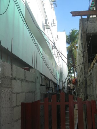 Giulius Boracay Italian Resort: Left white hotel, one of 2 construction zones 24/7 noise, rooms only 1,5 m separted by open co