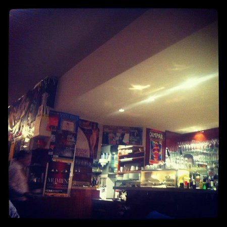 Bar with, behind it, traditional Viennese newspapered walls in Cafe Markusplatz